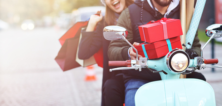 Foto de Portrait of happy couple with shopping bags after shopping in city smiling and huging - Imagen libre de derechos
