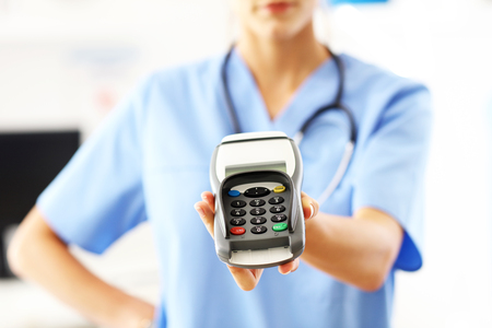 Photo pour Female doctor standing in her office with payment terminal - image libre de droit