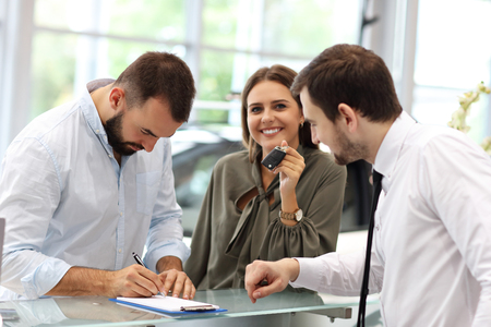 Photo for Confident young salesman explaining car features to the young attractive owners - Royalty Free Image