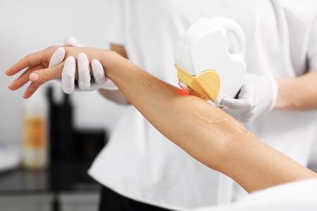 Photo pour Picture Of Beautician Giving Epilation Laser Treatment To Woman On Arms - image libre de droit