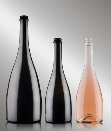 Photo pour front view closeup of three champagne bottles of different sizes blank with no label two black and one rose on grey background - image libre de droit