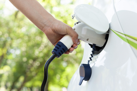 Photo for Hand holding an electric plug-in for charging electric car - Royalty Free Image