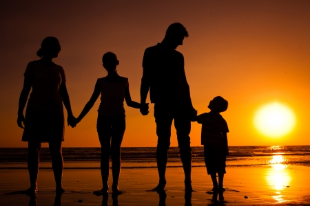 Photo for Silhouette of family on the beach at sunset - Royalty Free Image