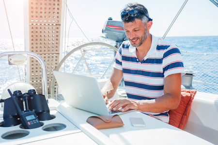 Foto per Man with laptop computer on sailboat - Immagine Royalty Free