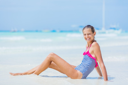 Photo for Girl in swimsuit sitting and having fun on tropical beach - Royalty Free Image