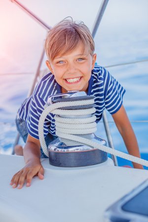 Foto de Little boy on board of sailing yacht on summer cruise. Travel adventure, yachting with child on family vacation. - Imagen libre de derechos