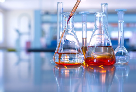 Foto de science laboratory glassware orange solution drop - Imagen libre de derechos