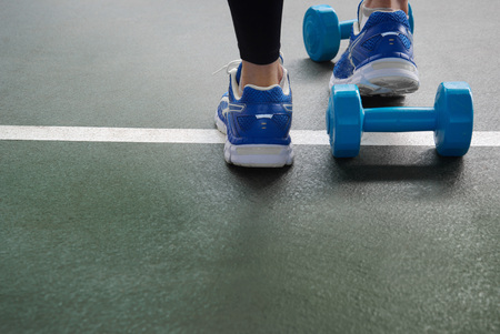 Foto de girl feet in sport shoes with blue dumbbell for exercise on dark green gymnasium floor background - Imagen libre de derechos
