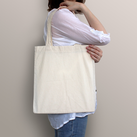 Photo pour Girl is holding blank cotton eco bag, design mockup. Handmade shopping bag for girls. - image libre de droit