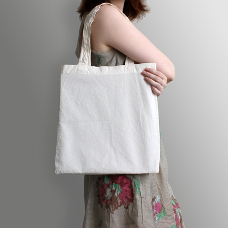 Foto de Girl is holding blank cotton eco tote bag, design mockup. Handmade shopping bag for girls. - Imagen libre de derechos