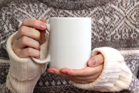 Foto de Girl in a warm sweater is holding white mug in hands. Mockup for winter gifts design. - Imagen libre de derechos