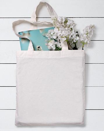 Foto de White blank cotton eco tote bag with flowers and notebook, design mockup. - Imagen libre de derechos