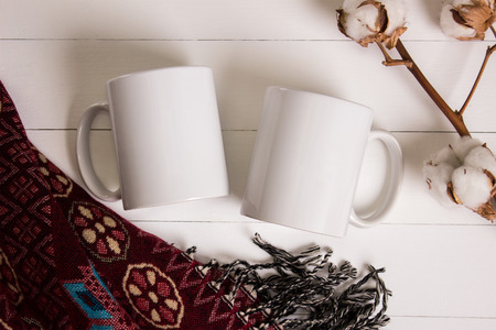 Photo pour Two white mugs, pair of cups, Mockup. Cozy atmosphere, wooden background, cotton and wool decorations for winter gifts. - image libre de droit