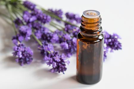 Photo pour A bottle of lavender essential oil with fresh lavender on a white background - image libre de droit