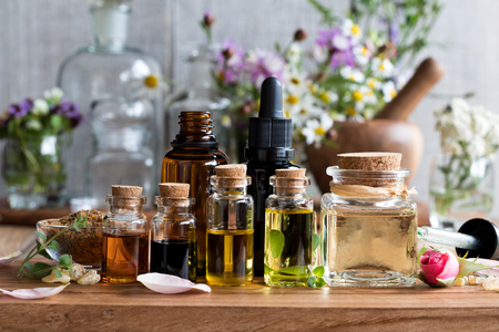Foto de Selection of essential oils, with herbs and flowers in the background - Imagen libre de derechos