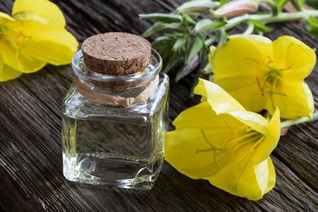Foto de A bottle of evening primrose oil on a wooden table with fresh evening primrose flowers in the background - Imagen libre de derechos