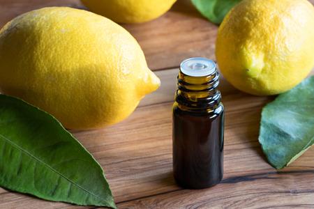 Foto de A dark bottle of lemon essential oil on a wooden table, with whole lemons in the background - Imagen libre de derechos