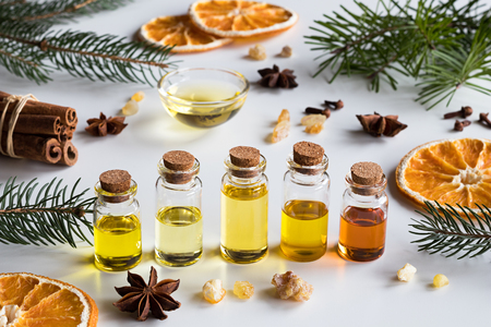 Foto de Christmas selection of essential oils and spices on white background: bottles of essential oil, spruce, fir, frankincense resin, star anise, cinnamon, clove, dried orange. - Imagen libre de derechos