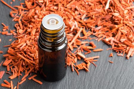 Foto de A bottle of sandalwood essential oil with sandalwood in the background - Imagen libre de derechos