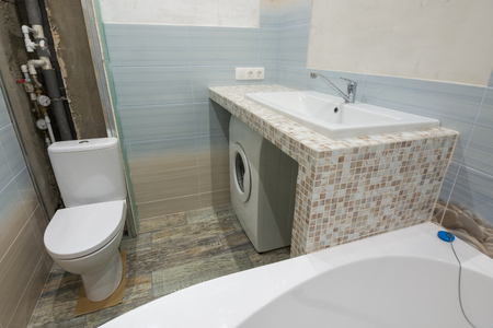 Photo for Unfinished repairs in the bathroom, a pedestal under the washbasin, under which there is a washing machine, and a toilet bowl - Royalty Free Image