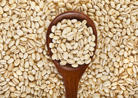 Foto per pearl barley with wooden spoon close up surface top view background - Immagine Royalty Free