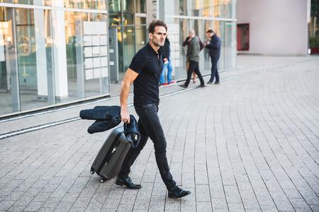 Foto de businessman comes with casual clothing and a trolley bag out of an office building - Imagen libre de derechos