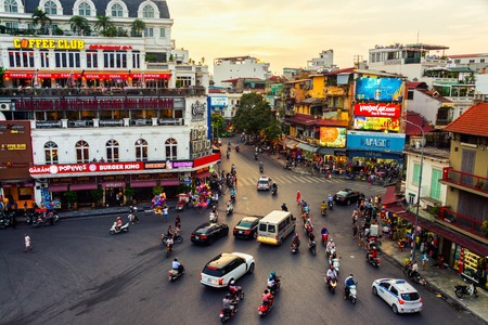 Photo for HANOI, VIETNAM - AUGUST 2, 2016: Car and people traffic in the city center. Typical cafes and restaurants. Sunset yellow sky - Royalty Free Image