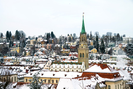 Photo pour St Gallen, Switzerland. Aerial view of historical buildings covered in snow in winter. Cathedral in St Gallen, Switzerland with bright blue sky - image libre de droit