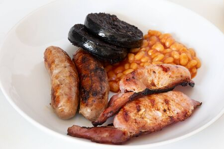 Photo for Cumberland sausages, back bacon, baked beans and black pudding in a white bowl - Royalty Free Image