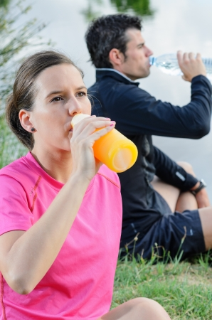 Young couple of athletes sitting and drinking water and oranje juice for recovering from trainning.