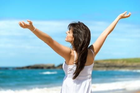 Photo pour Joyful happy woman raising arms to the sky on summer  Beautiful and blissful caucasian girl on beach vacation  Playa de Verdicio, Asturias, Spain  - image libre de droit