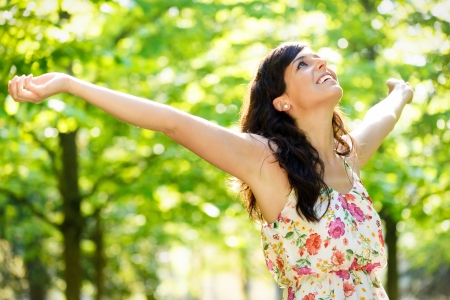 Photo pour Carefree happy woman in spring or summer forest park raising arms with happiness, hope and vitality. Caucasian girl relaxing and enjoying life on nature outdoors. - image libre de droit