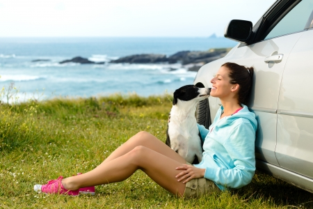 Foto de Happy woman and dog sitting outside car on summer travel vacation - Imagen libre de derechos