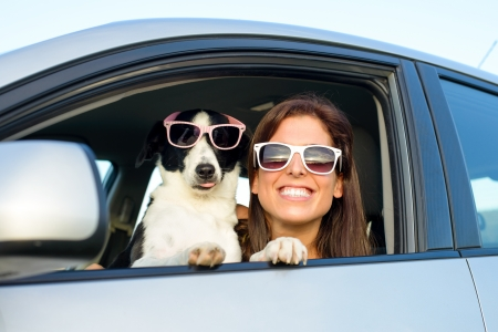 Photo pour Woman and dog in car on summer travel  Funny dog with sunglasses traveling  Vacation with pet concept  - image libre de droit