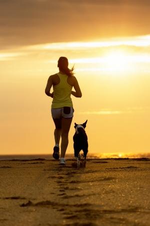 Foto de Woman and dog running toward the sun on summer beach in a beautiful golden sunset  Sport girl and her pet training together  - Imagen libre de derechos