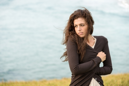 Foto de Sad shivery woman in brown sweater jacket hugging herself on late summer cold and windy day on sea background. Sadness, melancholia and heart broken concept. - Imagen libre de derechos