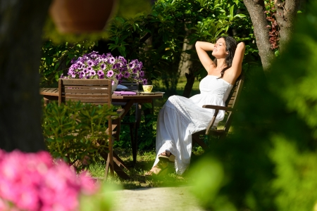 Happy woman resting in garden on summer sunny morning surrounded by flowers and trees. Young caucasian brunette relaxing and enjoying outdoors.