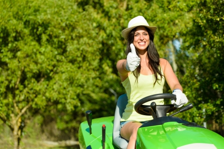 Photo pour Successful and happy female gardener riding garden tractor doing approval gesture with thumbs up. Woman riding lawn mower. Girl working on summer job. - image libre de droit