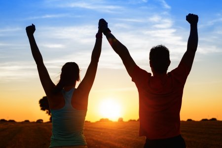 Photo pour Successful couple of young athletes raising arms to golden summer sunset sky after training  Fitness man and woman with arms up celebrating sport goals after exercising in countryside field  - image libre de droit