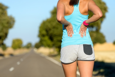 Photo pour Female runner athlete low back injury and pain. Woman suffering from painful lumbago while running in rural road. - image libre de droit