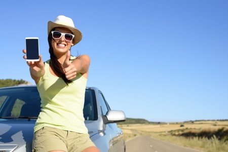 Foto de Young woman leaning on car showing cell phone screen and doing thumbs up gesture  Positive woman giving her approval to car insurance service  - Imagen libre de derechos