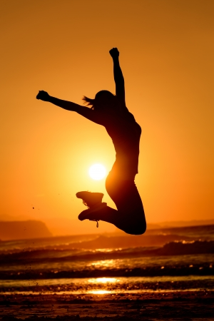 Foto de Successful woman jumping, dancing and having fun on sunset in beach  Freedom and happiness concept  Girl celebrating work out success  - Imagen libre de derechos