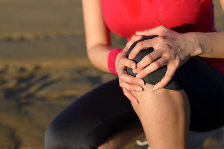 Photo pour Runner sport knee injury  Woman in pain while running in beach  Caucasian female athlete with painful kneecap  - image libre de droit