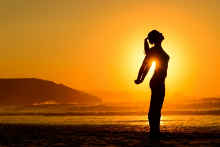 Foto de Fit woman doing yoga relaxing and breathing exercises on beach at summer sunset  Freedom, relax and harmony in nature  Female stretching arms alone  - Imagen libre de derechos