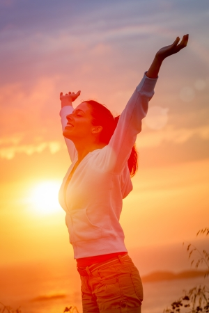 Photo pour Woman enjoying freedom and life on beautiful and magical sunset. Blissful girl raising arms feeling free, relaxed and happy. - image libre de droit