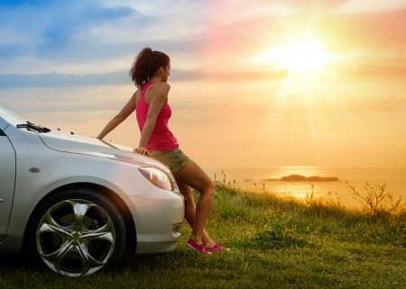 Photo for Female driver enjoying freedom and beautiful sunshine over the sea after driving to coast in summer vacation travel. Woman relaxing and taking a break to enjoy the scenery. - Royalty Free Image