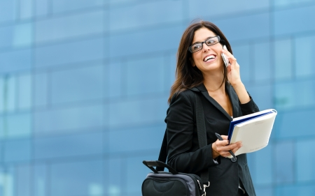 Photo for Successful businesswoman or entrepeneur taking notes and talking on cellphone while walking outdoor  City business woman working  - Royalty Free Image