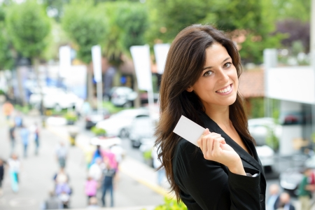 Photo pour Successful female car sales representative showing business card  in automobile trade fair  Beautiful brunette saleswoman outdoor  - image libre de droit
