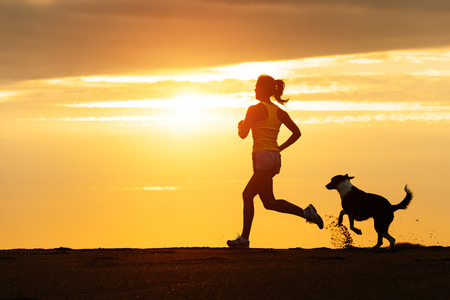 Foto de Woman and dog running free on beach on golden sunset  Fitness girl and her pet working out together  - Imagen libre de derechos