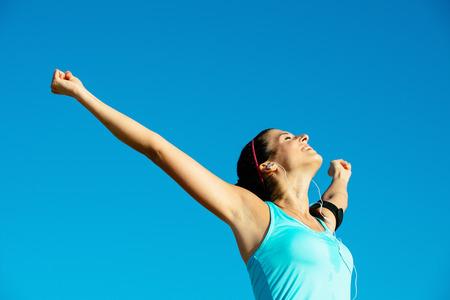Foto de Successful happy fitness woman raising arms to the sky after sport achievement outdoor  Sporty girl enjoying freedom  - Imagen libre de derechos